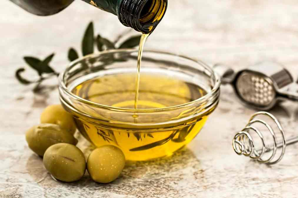 Picture shows Olive Oil being poured in a glass bowl with a few olives lying outside the bowl